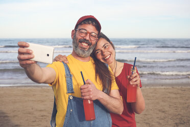 Couple with soft drinks taking selfie with smartphone on the beach - RTBF01176