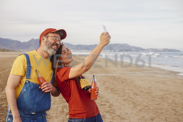 Couple with soft drinks taking selfie with smartphone on the beach - RTBF01179