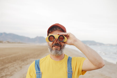 Bearded man using binoculars on the beach - RTBF01182