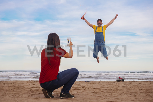 Woman taking smartphone picture of happy man  jumping on the beach - RTBF01185