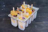 Homemade orange and lemon popsicles with edible flowers - SKCF00442