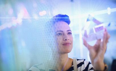 Innovative female entrepreneur examining glass cube prototype - HOXF03361