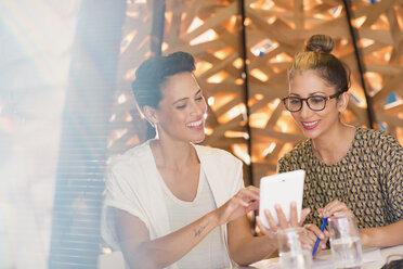 Smiling female creative businesswomen meeting, using digital tablet - HOXF03370