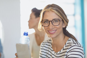 Portrait smiling, confident businesswoman with digital tablet and water bottle - HOXF03391