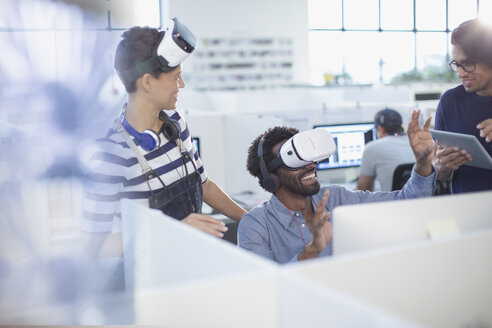 Computer programmers testing virtual reality simulators in office - HOXF03451