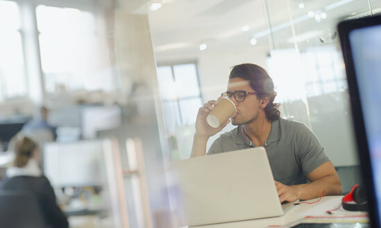 Creative businessman drinking coffee, working at laptop in office - HOXF03457