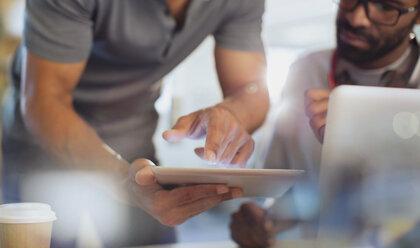 Close up businessmen using digital tablet - HOXF03478
