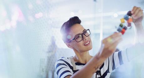 Curious, innovative female entrepreneur examining prototype - HOXF03481