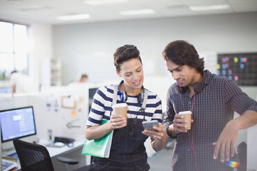 Creative business people drinking coffee and using smart phone in office - HOXF03493