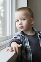 Portrait of cute boy standing by window at home - CAVF45732