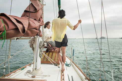 Friends talking while traveling in sailboat - CAVF45741