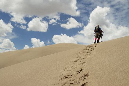 Low angle view of hiker walking in desert - CAVF45873