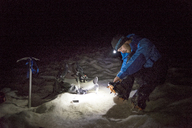 Hiker wearing crampon shoes while sitting on snowy field at night - CAVF45909