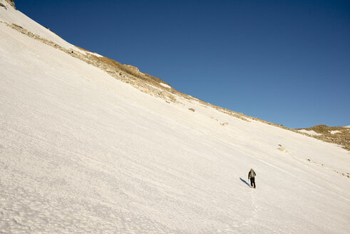 Rear view of man hiking on snowy field against clear blue sky - CAVF45912