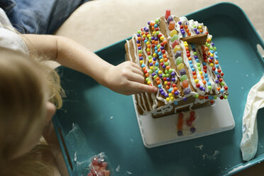 High angle view of girl decorating toy house at home - CAVF45927