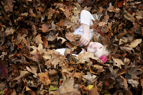 High angle view of cheerful girl lying in maple leaves during autumn - CAVF45936
