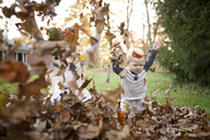Cheerful siblings playing with dry leaves in backyard - CAVF45954