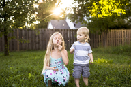 Playful siblings blowing dandelion in backyard - CAVF45963
