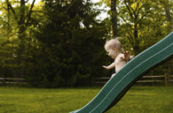 Shirtless boy playing on slide in backyard - CAVF45978
