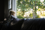Thoughtful boy looking through window while kneeling on sofa - CAVF45981