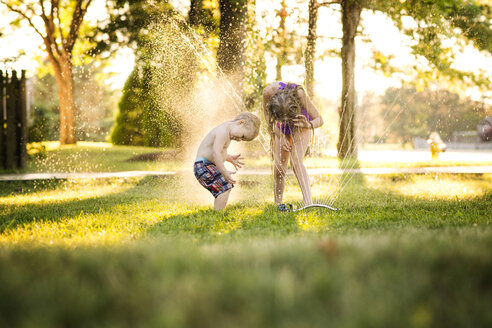 Cheerful siblings playing with water in backyard - CAVF45999