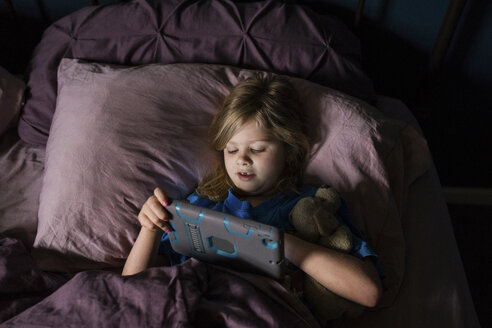 High angle view of girl using tablet computer while lying on bed at home - CAVF46023