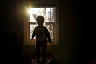 Silhouette boy standing by window in darkroom at home - CAVF46032