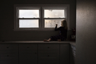 Girl making heart shape on condensed window while sitting on kitchen counter at home - CAVF46044