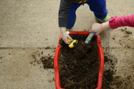 Cropped image of siblings playing with mud in yard - CAVF46065