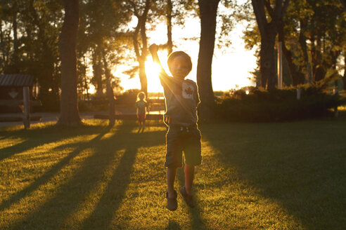 Siblings playing on grassy field in park during sunset - CAVF46092