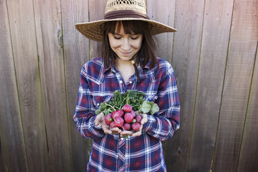 Smiling young female farmer holding radishes while standing against wooden fence - CAVF46203