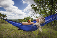 Woman holding apple while lying on hammock at field during vacation - CAVF46233