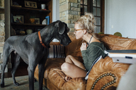 Woman looking at Great Dane while sitting on sofa - CAVF46344