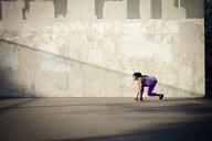 Woman in starting position on street ready to run by wall - CAVF46497