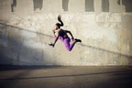 Side view of woman jumping in mid-air against wall - CAVF46503