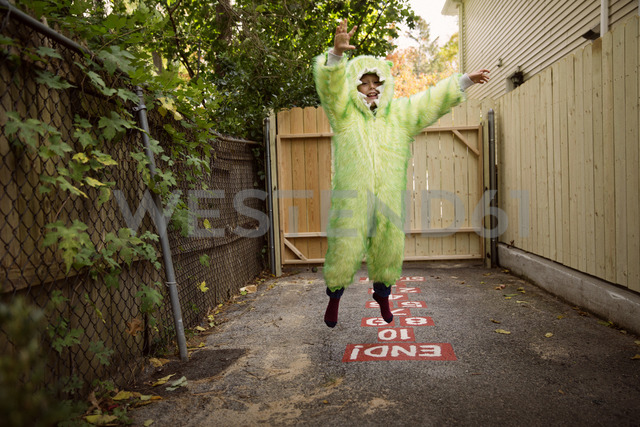 Portrait of boy wearing costume jumping while playing hop scotch at backyard - CAVF46593