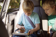 Boy using tablet computer while sitting in car - CAVF46602