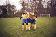 Full length of soccer players enjoying on playing field against trees - CAVF46650