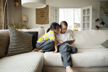 Sister looking at brother using tablet computer while sitting on sofa in living room - CAVF46704