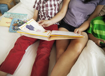 Midsection of mother reading book to son while sitting beside daughter on bed at home - CAVF46716