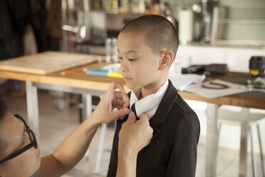 Father adjusting son's necktie at home - CAVF46737