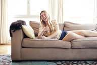 Cat looking at happy woman lying on sofa in brightly lit living room - CAVF46749