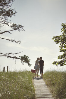 Rear view of couple kissing while standing on boardwalk amidst field against sky - CAVF46824