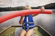 Girl holding noodle float while sitting in boat - CAVF46890