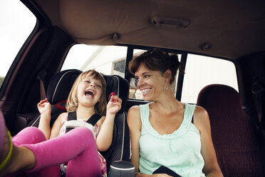 Cheerful grandmother and granddaughter sitting in car - CAVF46893