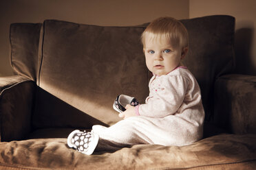 Portrait of baby girl sitting on armchair at home - CAVF46905