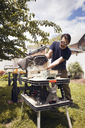 Man cutting wood at table saw while standing in yard - CAVF46908