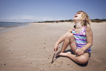 Happy girl with head back sitting on sand at beach - CAVF46911