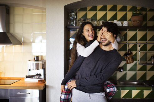 Cheerful girlfriend covering boyfriend's eyes while standing at home - CAVF47045
