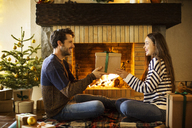 Happy couple holding Christmas present by fireplace at home - CAVF47063